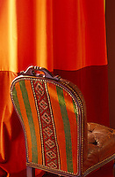A buttoned leather chair with a colourful fabric back is placed against an orange curtain