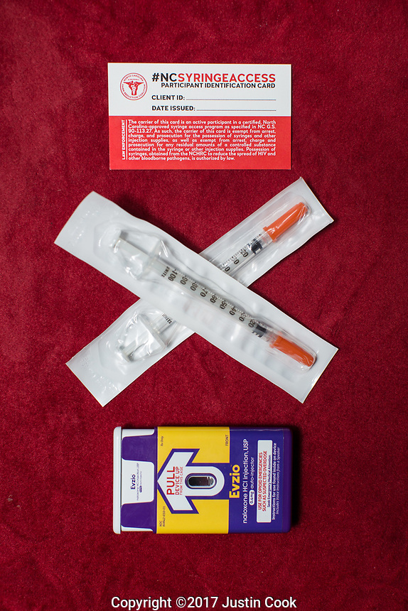 Top to bottom: A North Carolina syringe access card; Sterile syringes; and A Narcan (Naloxone) injector which blocks and reverses the effects of heroin and other opioids. The card exempts carriers from arrest and prosecution for possession of needles, other drug paraphernalia, and trace amounts of heroin. All are available at the Twin City Harm Reduction Collective, a needle exchange for addicts, at Green Street Church in Winston-Salem, NC.
