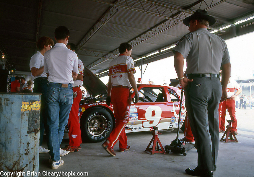 State troopers stand guard as crewmen work on the #9 Ford Thunderbird of driver Bill Elliott in preparation for the Southern 500 at Darlington Raceway in Darlington SC on September 1, 1985. (Photo by Brian Cleary/www.bcpix.com)