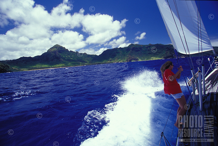 Woman sailing yacht in rough seas off Kauai's East shore, with blue sea and red shirt