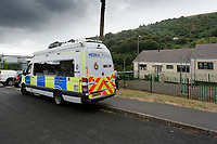 Pictured: Police at the house where the body of David Gaut was discovered in New Tredegar, Wales, UK. Wednesday 08 August 2018<br /> Re: Three men have been arrested after a man was found dead at a house in New Tredegar, Wales, UK.<br /> David Gaut, 54, was found in Long Row, in the Elliots Town area of New Tredegar, on Saturday, August 4.<br /> Two two-storey terraced homes, owned by Caerphilly council, have been cordoned off and police officers are patrolling the area. <br /> David Gaut was jailed for life in July 1985 when he was 21 years old, for the murder and torture of17-month old Chi Ming Shek