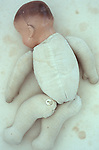 Vintage baby doll with padded fabric body lying face down naked on antique paper