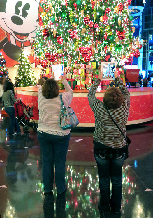 """Tourist snap photos of the decorated trees at the annual """"Christmas Around The World"""" exhibit at the Museum of Science and Industry in Chicago. (Photo by Jamie Moncrief)"""