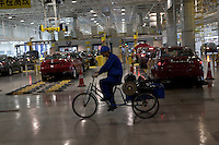A car worker uses a tricycle to transport parts at a Shanghai Automotive Industry Corporation (SAIC) factory building Roewe cars in Shanghai, China on November 10, 2009.
