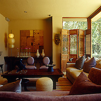 This living room is filled with interesting objects and furniture set against a backdrop of walls painted a warm yellow ochre