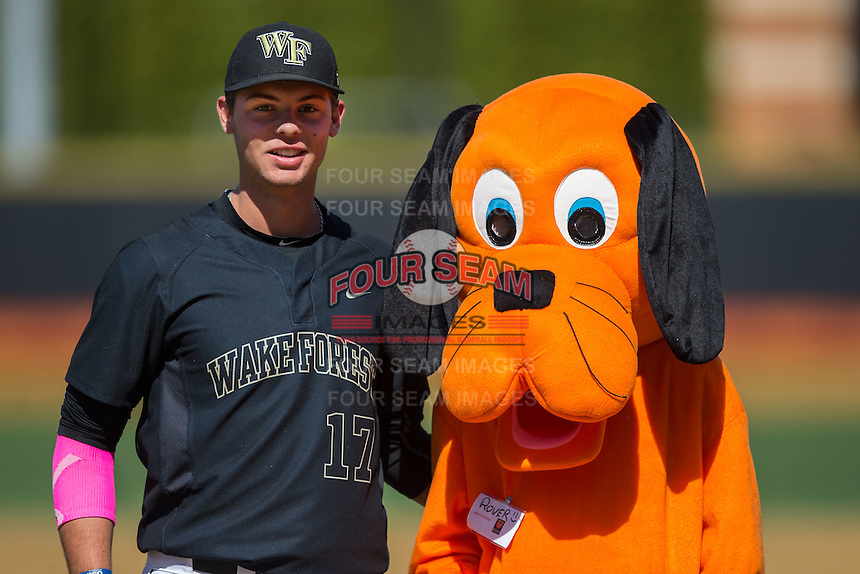 """Bruce Steel (17) of the Wake Forest Demon Deacons poses with """"Rover"""" following the ceremonial first pitch on """"Bark in the Park"""" day prior to the game against the Florida State Seminoles at David F. Couch Ballpark on April 16, 2016 in Winston-Salem, North Carolina.  The Seminoles defeated the Demon Deacons 13-8.  (Brian Westerholt/Four Seam Images)"""