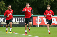 Pictured: (L-R) Neil Taylor, Sam Vokes and Joe Allen run on the pitch. Monday 02 October 2017<br /> Re: Wales football training, ahead of their FIFA Word Cup 2018 qualifier against Georgia, Vale Resort, near Cardiff, Wales, UK.