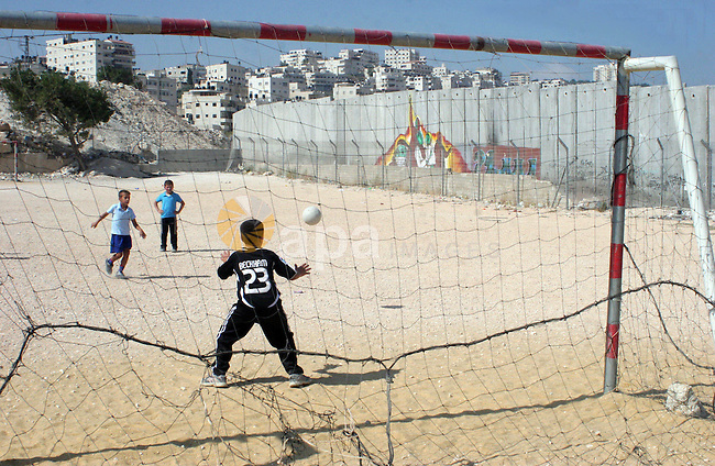 palestinian students play football in playground after they come back from their school next the separation wall near the west bank village of anabta.