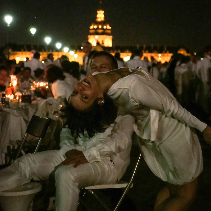 Dîner en Blanc at the Esplanade des Invalides, Paris. This was the 26th year of the Dinner in White tradition in Paris. Attendance is by invitation only and guests are told the location just one hour in advance. Each has to bring a guest, travel by public transport, and be dressed all in white, with a white picnic table, chairs, wine, flowers and food. Approximately 12,000 people took part, covering many of the bridges in Paris and their surroundings. Thursday 12th June 2014.