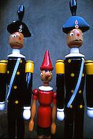 Statuette in legno di Pinocchio con i due carabinieri esposte a Collodi.