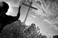 Catholic followers bath the wooden cross in the sea during the annual Holy Week ritual (Lavado de la cruz) in Santa Elena, Ecuador, 3 April 2012.