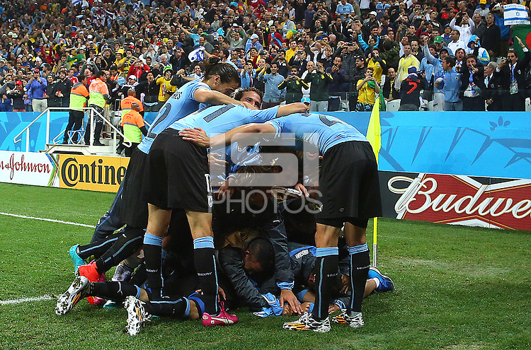 Luis Suarez of Uruguay is mobbed by team mates after scoring the winning goal, 2-1