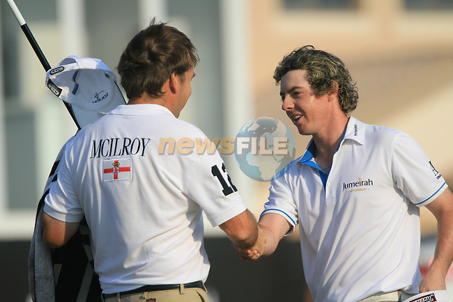 Rory McIlroy shakes his caddy's hand after finishing his round on the 18th green during the Final Day of the Dubai World Championship, Earth Course, Jumeirah Golf Estates, Dubai, 28th November 2010..(Picture Eoin Clarke/www.golffile.ie)