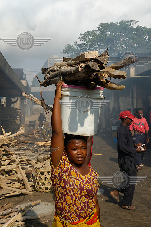 Young woman with wood for frying fish at the city's Magogoni fish market.