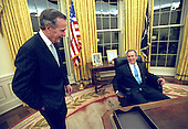 United States President George W. Bush sits at his desk in the Oval Office for the first time on Inauguration Day, Saturday, January 20, 2001. He talks with his father, former U.S. President George H.W. Bush, left..Mandatory Credit: Eric Draper - White House via CNP