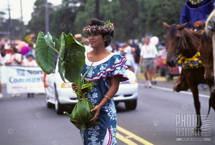Woman carries culturally significant kalo (taro) plant during parade as part of Aloha Week Festivals, Big Island