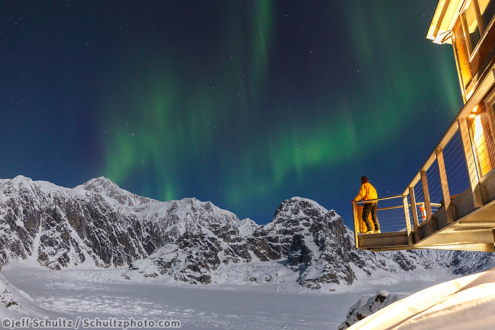 Visitor views the Aurora Borealis (aka: Northern Lights ) from the observation deck of the Sheldon Chalet in the Ruth Glacier and Amphitheater. Denali (aka: Mt. Mckinley) and the Alaska Range in background.  Winter <br /> <br /> Photo by Jeff Schultz/SchultzPhoto.com  (C) 2017  ALL RIGHTS RESERVED