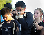 Classmate Victor Gardos, center, is overwhelmed with emotion as students gather around a memorial  during a vigil  at East Hartford High School for Robert Swain III, a three sport athlete who graduated from EHHS last month. Swain and his brother La'Andrew Evans-Swain, 16, were killed early Sunday morning in a one car accident on Forest Street in East Hartford. A memorial service is planned for the younger Swain at Manchester Regional Academy Wednesday.  (Jim Michaud / Journal Inquirer)