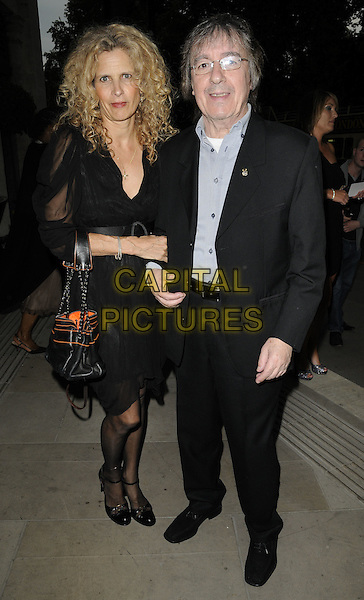 SUZANNE & BILL WYMAN .At the Bunbury's Big 25th Birthday Ball, Grosvenor House Hotel, Park Lane, London, England, UK, May 7th 2011..full length black dress sheer sleeve bag suit married couple husband wife .CAP/CAN.©Can Nguyen/Capital Pictures.