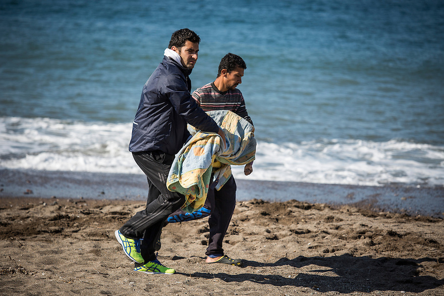 October 30, municipal workers carried a boy whose body washed ashore in the village of Petra, two nights after a boat with about 300 immigrants onboard crashed off the coast of Turkey.