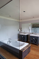 Two separate washstands and freestanding bath in a guest bathroom in Whitehouse, a guest house in Chillington, Devon