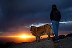 Hiker and dog watching sunset through storm clouds from the Santa Catalina Mountains, Coronado National Forest, Arizona