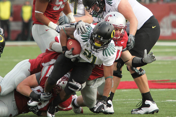 Washington State linebacker, Alex Hoffman-Ellis (#17), and a host of other Cougar tacklers bring down Oregon running back LaMichael James (#21) during the Cougars Pac-10 conference tilt at Martin Stadium in Pullman, Washington, on October 9, 2010.  The Ducks broke open a tight game in the fourth quarter to win, 43-23.