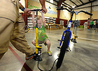 NWA Democrat-Gazette/ANDY SHUPE<br /> Keith Sams (left), a volunteer and member of the trail committee and Felix Suel, 5, work together Friday, Sept. 11, 2015, to pump up the tires on a bicycle being assembled at John Tyson Elementary School in Springdale. Volunteers assembled the last 32 bikes of a total 850 bikes funded by a grant from the Walton Family Foundation.