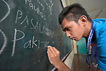A student writes on the blackboard in an Alternative Learning System class, sponsored by the Kapatiran-Kaunlaran Foundation (KKFI) in the Tondo neighborhood of Manila, Philippines. <br /> <br /> KKFI is supported by United Methodist Women.