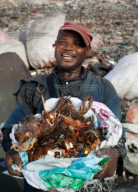 A man who scavenges for saleable items in the Olusosun dump shows a bag of copper wires that he has collected. The Olusosun dump is Nigeria's largest rubbish dump comprising over 100 acres of waste and is believed to be the largest in Africa.