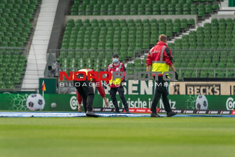 Vor dem Spiel werden die grossen Banner auf dem Rasen ausbreitet - Die Mitarbeiter mit CORONA Gesichtsmaske<br /><br />Sport: Fussball: 1. Bundesliga: Saison 19/20: <br />26. Spieltag: SV Werder Bremen vs Bayer 04 Leverkusen, 18.05.2020<br /><br />Foto ©  gumzmedia / Nordphoto / Andreas Gumz / POOL <br /><br />Nur fŸr journalistische Zwecke! Only for editorial use!<br /> DFL regulations prohibit any use of photographs as image sequences and/or quasi-video.