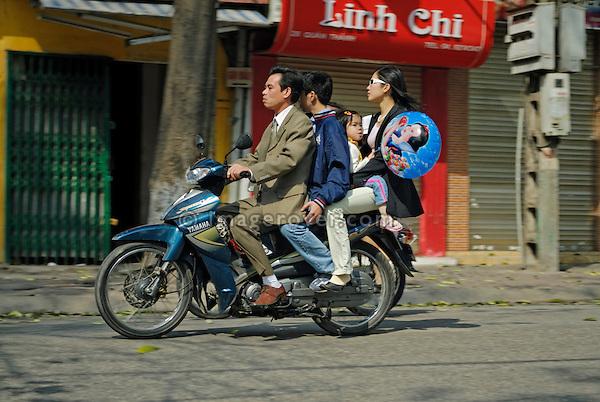 Asia, Vietnam, Hanoi. Hanoi old quarter. Family with two children riding on motorbike through Hanoi.