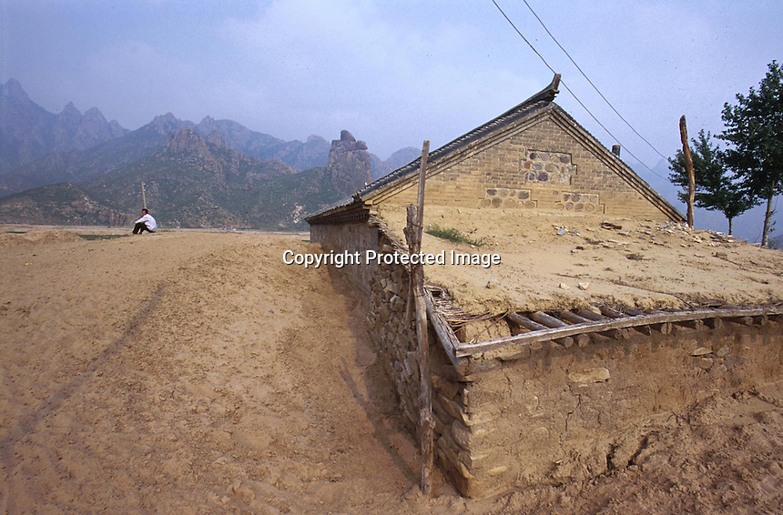 Moving sand swamps a village house in LangTou Gou, Fang Ning, China.  Droughts and increasing desertification are causing ever-greater environmental problems in northern China...WONG / SINOPIX