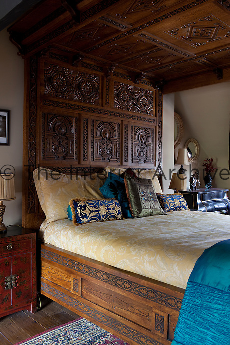 A heavily carved wooden four-poster bed dressed with cushions and a yellow floral pattern bed cover