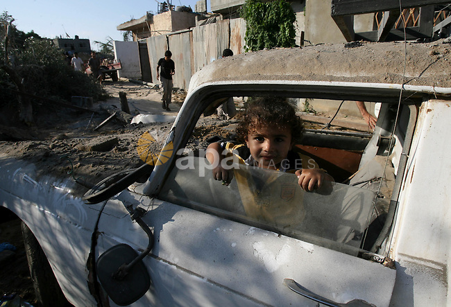 A Palestinian girl sits inside the rubble of a car as she return to her house during an humanitarian truce in Khan Younis in the southern Gaza Strip on July 26, 2014. Palestinians retrieved dozens of bodies from the rubble of Gaza homes during a brief truce in the fighting, raising to over 900 the overall death toll of Israel's onslaught on the territory since July 8, medics said. Photo by Eyad Al Baba