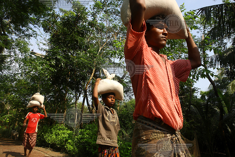 Men and children carry sandbags on their head which will be used to make barriers against the floodwaters. Thousands of people were displaced in Shyamnagar Upazila, Satkhira district after Cyclone Aila struck Bangladesh on 25/05/2009, triggering tidal surges and floods....