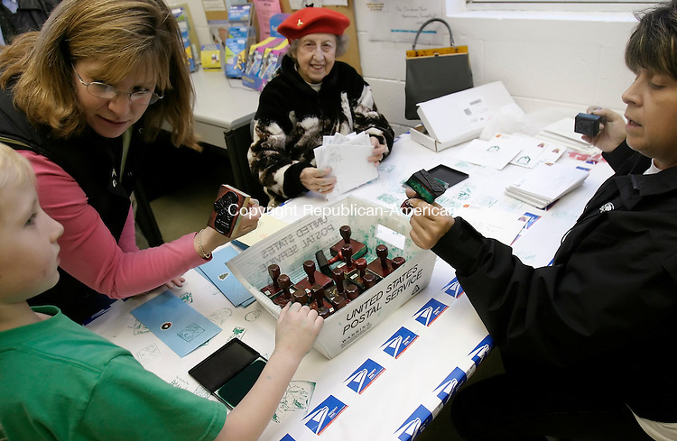 BETHLEHEM, CT 30 November 2005 -113005BZ07- From left- Emmett Wojtczak, 7, of Morris; Janice Wojtczak, of Morris;  Caroline Lounsbury, of Bethlehem; and Marian Muscio, of Bethlehem; stamp Christmas cards at the Bethlehem Post Office Wednesday afternoon.  Each  stamp has a picture of a Christmas or Hanukkah scene and is available in the lobby to decorate holiday cards.<br />  Jamison C. Bazinet Republican-American