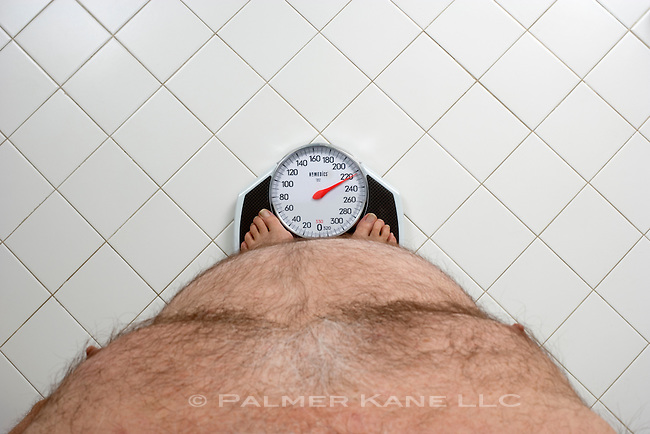 Overweight Man weighing himself on bathroom scale
