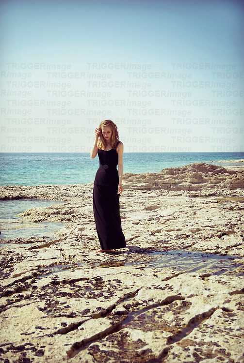 Portrait of young woman on the beach wearing a long black dress removing her hair from her face while looking down
