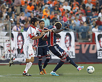 New England Revolution forward Saer Sene (39) passes the ball as D.C. United defender Daniel Woolard (21) defends. In a Major League Soccer (MLS) match, the New England Revolution (blue) tied D.C. United (white), 0-0, at Gillette Stadium on June 8, 2013.