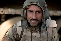 Iraqi tank driver Haedan Manshwd from the 1st company, 1st armour battalion of the 1st mechanized Iraqi Army Brigade seeks cover in back of his tank  while conducting  patrols, check points and observation posts on code name route Michigan, the main road of Ramadi in the week during the national election on WED Dec 14 2005 in Ramadi, Iraq. 1st company is part of the first armor battalion of the New Iraqi Army. it has started its training in January 2005. after 50 days their 35 russian and chinese built T 55 tanks begun conducting operations under the guidance of a US military adivisor team. in April 2005 they patrolled in the Abu Ghraib area concluding their first significant mission. While these old tanks are rolling on the ramadi streets more modern T72s are getting ready to become fully operational in Taji, their main base. the Iraqi army wanted to show their power in ramadi during the Dec 15 elections displaying their new armour company. but like all the other Iraqi forces they are not going to secure the polling sites, staying in the rear with the rest of the iraqi and coalition forces. T 55s are very old tanks. production begun in the late 50s to the late 70s. athough obsolete many countries still use the T55 as their main heavy armoured combat vehicle. slow, heavvy and with very little room for the crew it suffers from many mechanical problems constantly challenging the iraqi mechanics and engineers.