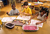 MR / Schenectady, New York. Howe International Magnet School (urban public magnet school with international theme). Second grade students (Age 7; Two are African-American) stamp potato prints using paint they made from natural materials (beets and cornstarch). MR: CN-gr2-CR. © Ellen B. Senisi