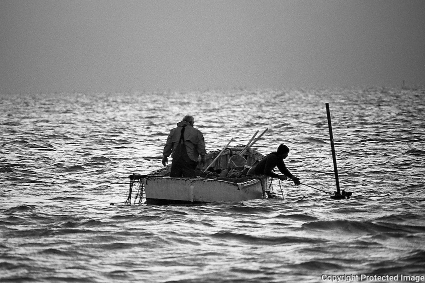 Hugh Styron Jr. and Shane Moldenhaur attach a line to the footing stake in rough seas during a mid-October haul at Evergreen Slough in Core Sound. Men work in skiffs but also enter the water during the last stages of the long-haul fishing operation.