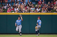 Lane Adams (8) of the Northwest Arkansas Naturals catches a ball in left field as Brett Eibner (24) looks on during a game against the Springfield Cardinals at Hammons Field on August 23, 2013 in Springfield, Missouri. (David Welker/Four Seam Images)