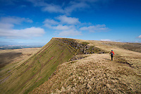Female hill walker hiking on Carmarthen Fans - Bannau Sir Gaer with Picws Du in distance, Black Mountain, Brecon Beacons national park, Wales