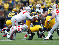 Michigan Wolverines running back De'Veon Smith (4) backs through Ohio State Buckeyes defensive lineman Michael Hill (77) and defensive lineman Tyquan Lewis (59) during the first quarter of the NCAA football game in Ann Arbor on Nov. 28, 2015. (Adam Cairns / The Columbus Dispatch)