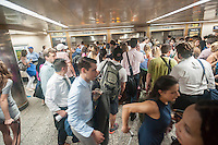 Thousands descend to board the Cannonball at Penn Station in New York to get out of the city for the Memorial Day weekend on Friday, May 27, 2016. Every Friday during the summer the train, consisting of double-decker cars pulled by a powerful dual-mode locomotive, will run express to Westhampton on Long Island making the 76 mile trip in 94 minutes. From Westhampton it will continue to points east arriving at the tip of the island, Montauk. On Sundays the train will reverse and return to Penn Station. The train is the only named run on the railroad. The trip from Penn Station to the Montauk terminal is 117 miles making the train the longest run on the railroad. (© Richard B. Levine)