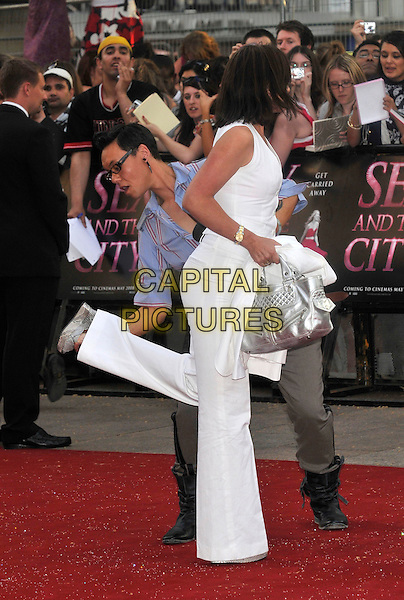 "GOK WAN & DAVINA McCALL.Red Carpet Arrivals at the ""Sex And The City"" Movie World Premiere, Odeon Leicester Square, London, England, UK,.May 12th 2008..full length white trousers showing wedges shoes silver bag funny looking leg up.CAP/PL.©Phil Loftus/Capital Pictures"