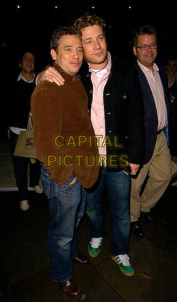 DEXTER FLETCHER & JAMIE OLIVER.The VIP private viewing of portraits by artist David Hockney at the National Portrait Gallery, London, UK..October 11th, 2006 .Ref: CAN.full length brown black jacket coat mobile phone.www.capitalpictures.com.sales@capitalpictures.com.©Can Nguyen/Capital Pictures.