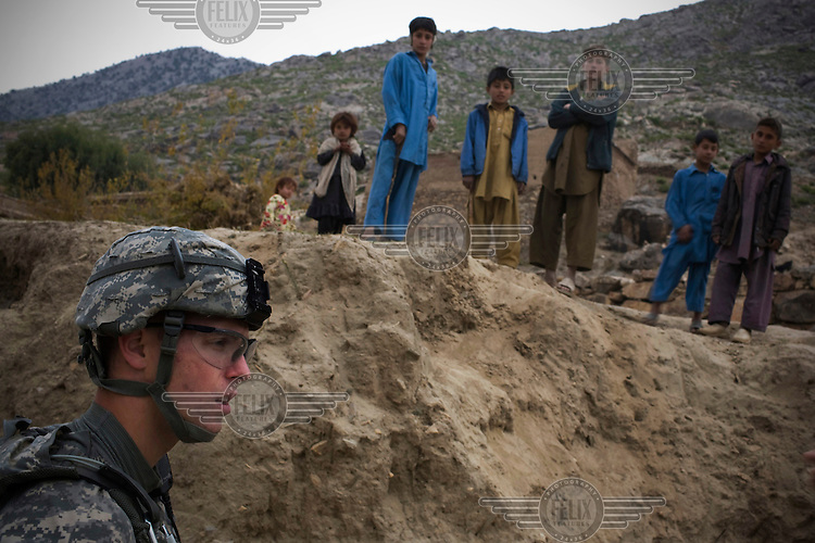 Lieutenant Fynch, 3rd Platoon, Charlie Company, 1-26 Infantry passes children on a mission to maintain support in the pro-coalition village of Manugai in the Pesh Valley. On the previous day an improvised explosive device (IED) had been found in the village ahead of an American convoy.